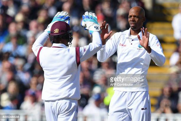 West Indies' Roston Chase celebrates with West Indies' Shane Dowrich after taking the wicket of England's Dawid Malan during play on day 2 of the...