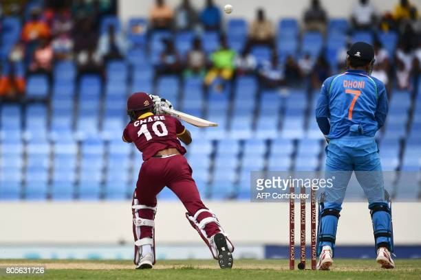 West Indies' Roston Chase is bowled off India's Kuldeep Yadav as wicketkeeper MS Dohni looks on during the fourth One Day International match between...