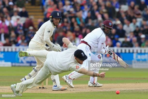 West Indies' Roston Chase watches as England fielder Ben Stokes attempts to catch the ball during play on day 3 of the first Test cricket match...