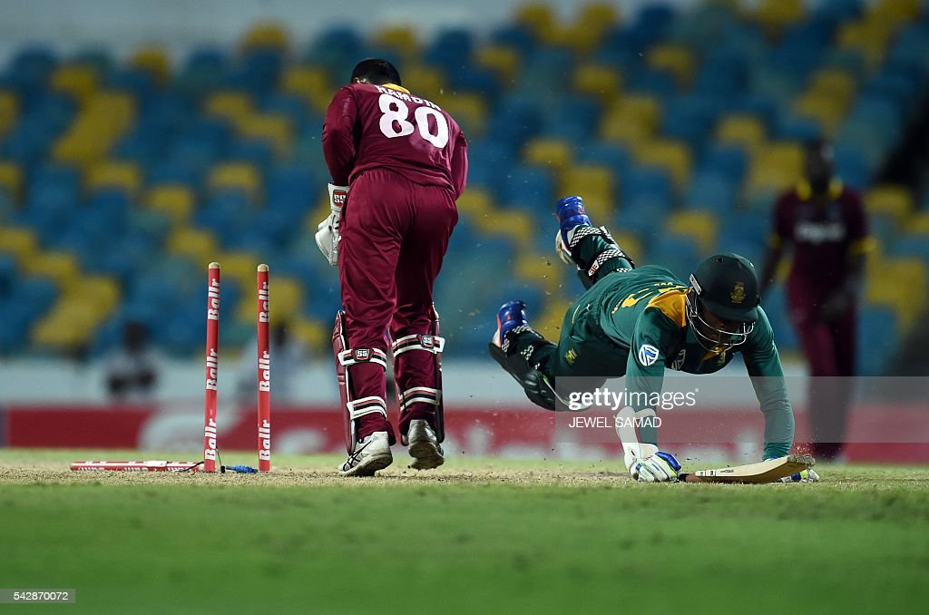 West Indies wicketkeeper Denesh Ramdin (L) breaks the wicket to run-out South African cricketer Kagiso Rabada (R) during the 9th One Day International match of the Tri-nation Series between South Africa and West Indies at the Kensington Oval stadium in Bridgetown on June 24, 2016. / AFP / Jewel SAMAD