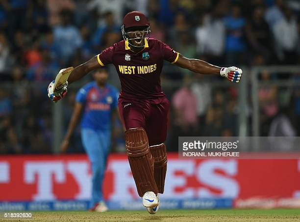 West Indies's Andre Russell celebrates after scoring the winning runs during the World T20 men's semifinal match between India and West Indies at The...