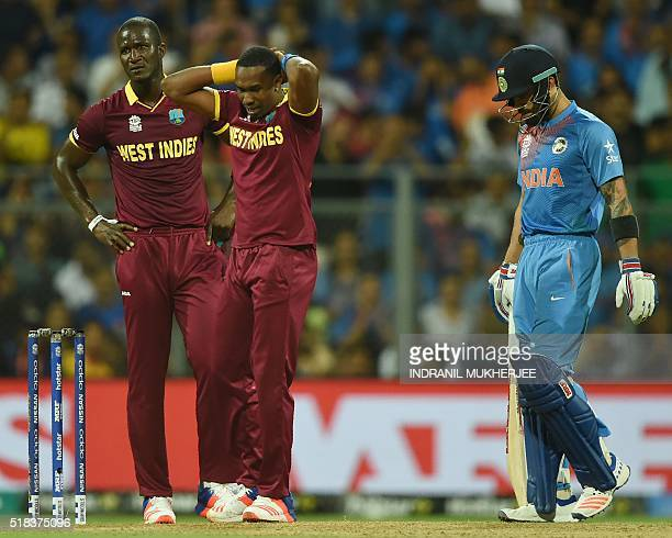 West Indies's captain Darren Sammy and teammate Dwayne Bravo react after failing to run out India's Virat Kohli during the World T20 men's semifinal...