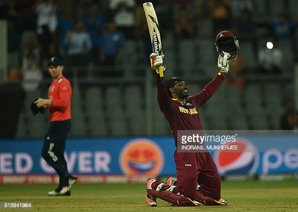 West Indies's Chris Gayle celebrates after scoring his century as England's captain Eoin Morgan walks past during the World T20 cricket tournament...