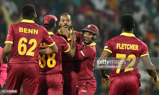 West Indies's Chris Gayle celebrates with teammates after taking the wicket of South Africa's batsman David Miller during the World T20 cricket...