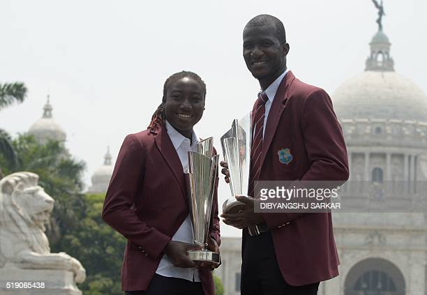 West Indies's cricket captains Stafanie Taylor and Darren Sammy pose for a photograph with the World T20 cricket tournament trophies one day after...