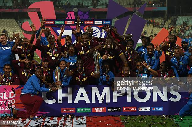 West Indies's Darren Sammyleads teammates and members of the West Indies women's team as they pose with the trophy after victory in the World T20...