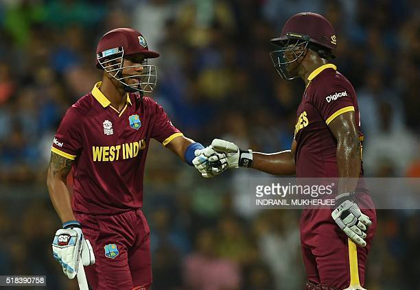 West Indies's Lendl Simmons and Johnson Charles bump fists during the World T20 semifinal match between India and West Indies at The Wankhede Cricket...