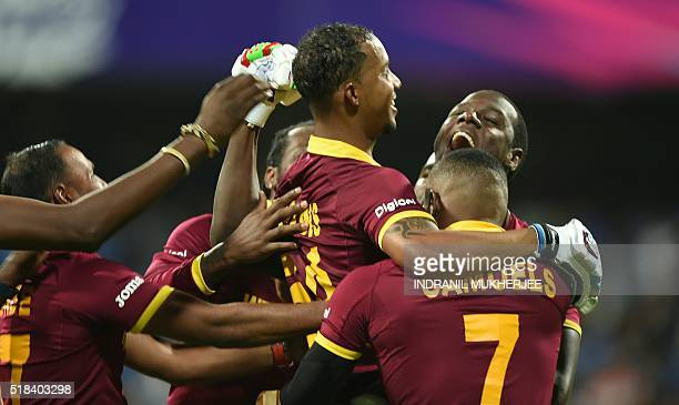 West Indies's Lendl Simmonsis held aloft by teammates as they celebrate after victory in the World T20 cricket tournament second semifinal match...