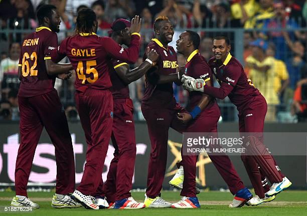 West Indies's Sulieman Benn Chris Gayle captain Darren Sammy Andre Russell Dwayne Bravo and Denesh Ramdin celebrate after the wicket of England's...