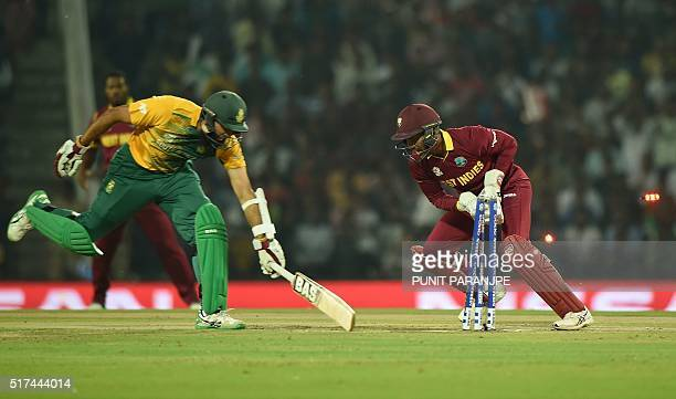 West Indies's wicketkeeper Denesh Ramdin successfully runs out South Africa's batsman Hashim Amladuring the World T20 cricket tournament match...
