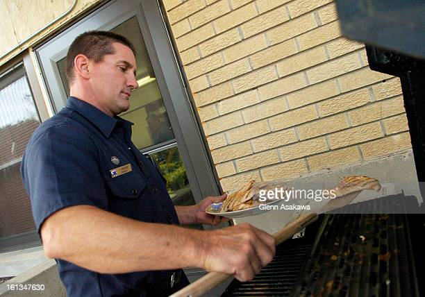 FE26FTFIRE West Metro firefighters Tim Driscoll <cq> grills chicken breasts outside of Station 8 in Lakewood for grilled chicken club sandwiches...
