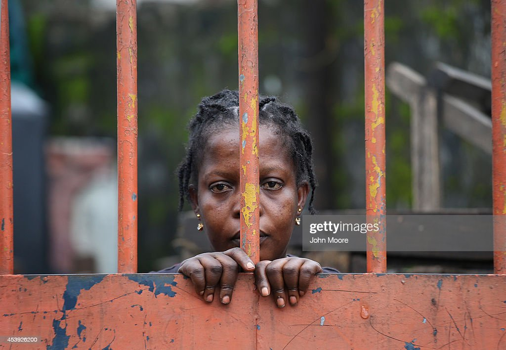 A West Point slum resident looks from behind closed gates on the second day of the government's Ebola quarantine on their neighborhood on August 21, 2014 in Monrovia, Liberia. The government delivered bags of rice, beans and cooking oil to residents, who are forbidden from leaving the seaside slum, due to the Ebola outbreak in their community. More than 1,200 people have died due to the Ebola epidemic in West Africa.