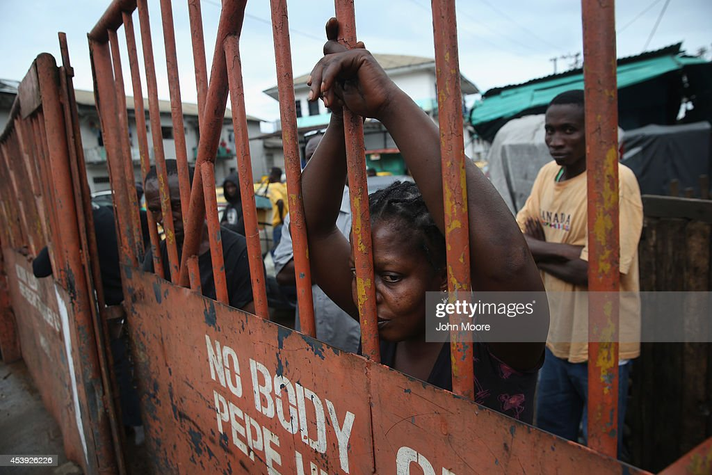 West Point slum resident looks from behind closed gates on the second day of the government's Ebola quarantine on their neighborhood on August 21...