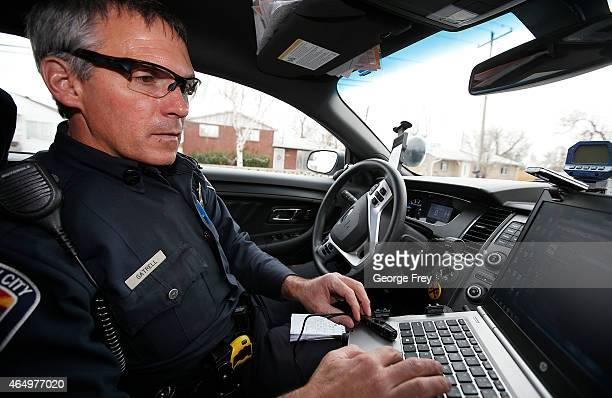 West Valley City patrol officer Gatrell hooks up a body camera recorder to his laptop computer to add an incident number to the video after he took a...
