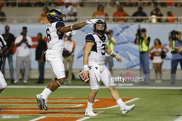 West Virginia Mountaineers quarterback Skyler Howard is congratulated by West Virginia Mountaineers wide receiver Daikiel Shorts after running for a...
