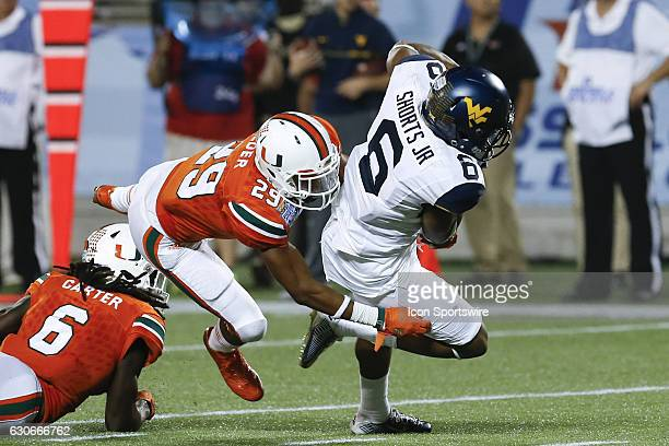 West Virginia Mountaineers wide receiver Daikiel Shorts is tackled from behind by Miami Hurricanes defensive back Corn Elder after catching a pass...