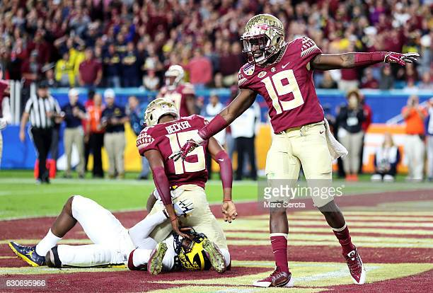 J Westbrook and Carlos Becker III of the Florida State Seminoles celebrate breaking up a apass in the second quarter against the Michigan Wolverines...