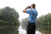 Westbrook Police Officer Garrett McCarthy uses binoculars to look out on the Presumpscot River in search of a large snake estimated at 10 feet in...