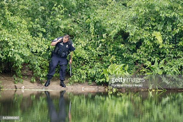 Westbrook Police Officer Phil Robinson scans the banks of the Presumpscot River in search of a large snake estimated at 10 feet in length that was...