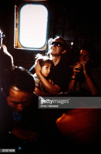A western civilian clutches his son as a Marine Corps Sea Stallion helicopter lifts off from the Defense Attache Office compound in Saigon Vietnam...