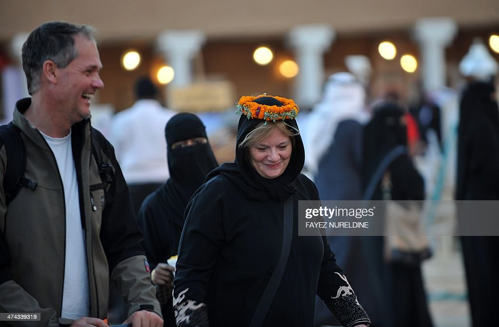 A western couple attends the Janadriyah festival of Heritage and Culture held in the Saudi village of Al-Thamama, 50 kilometres north of the capital Riyadh, on February 22, 2014.