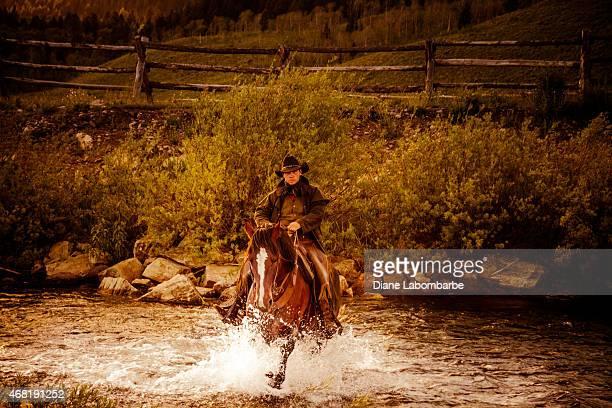 Western Cowboy Bandit Rides His Horse Through A Creek