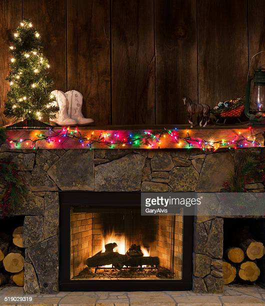 Western fireplace w/Christmas decor-fire,boots,lighted tree,sleigh,lantern