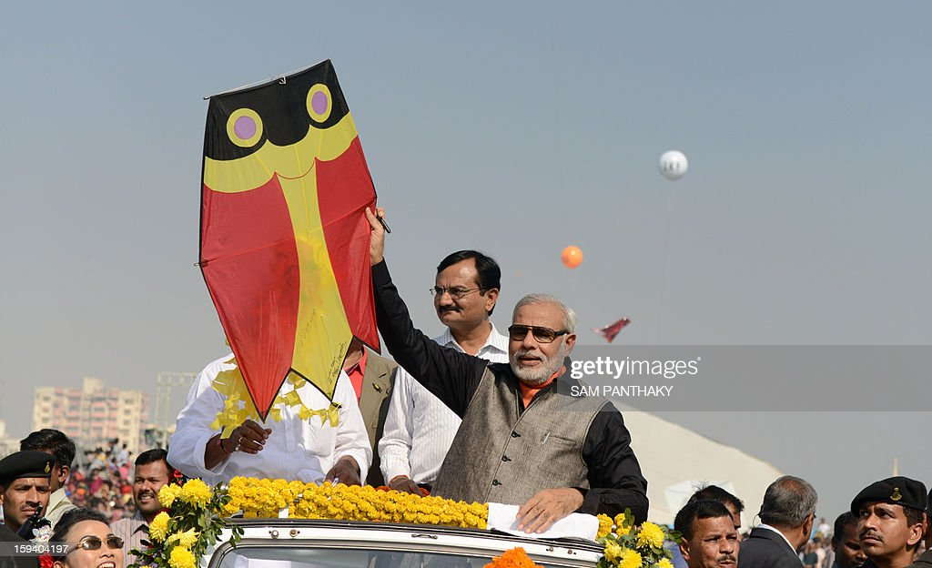 Western India's Gujarat state Chief Minister, Narendra Modi, (C) holds a kite after putting his autographs on it, inaugurating the 25th International Kite Festival 2013 in Ahmedabad on January 13, 2013. The first edition of this festival was held in 1989 and was attended by Sir Edmund Hillary, legendary mountaineer and the first person to scale Mt. Everest. AFP PHOTO/ Sam PANTHAKY