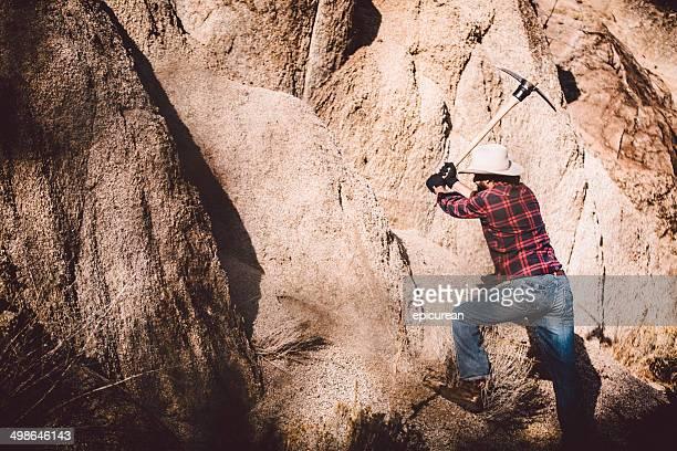Western Man swings pickaxe against rock face