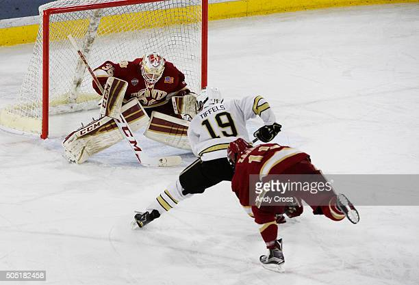 Western Michigan Broncos forward Frederik Tiffels charges to the net and towards University of Denver Pioneers goalie Tanner Jaillet and University...