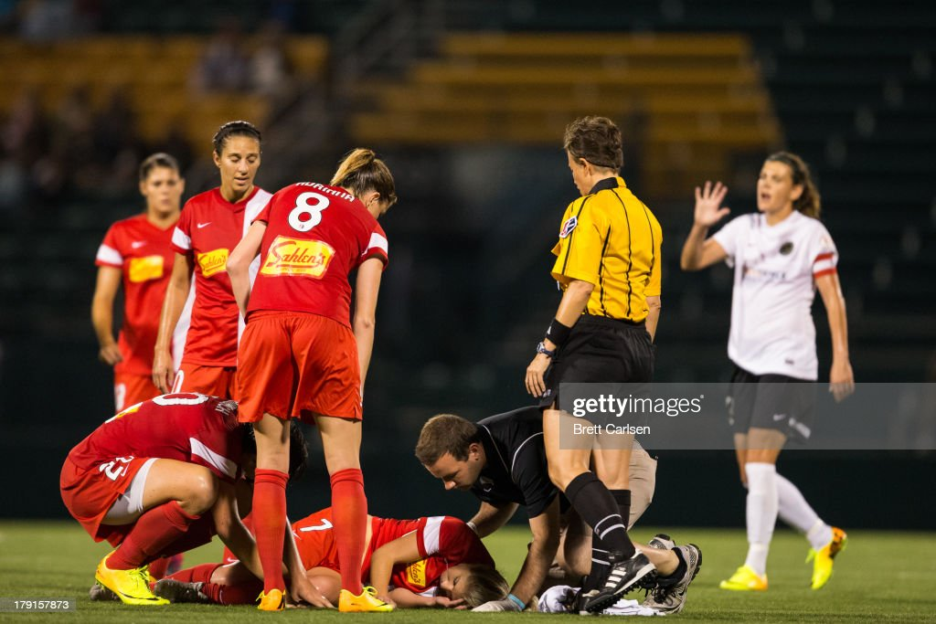 Western New York Flash's McCall Zerboni #7 is attended to by a team trainer and teammate Abby Wambach #20 following a midair collision with a member of Portland Thorns FC in the National Women's Soccer League Championship at Sahlen's Stadium August 31, 2013 in Rochester, New York.