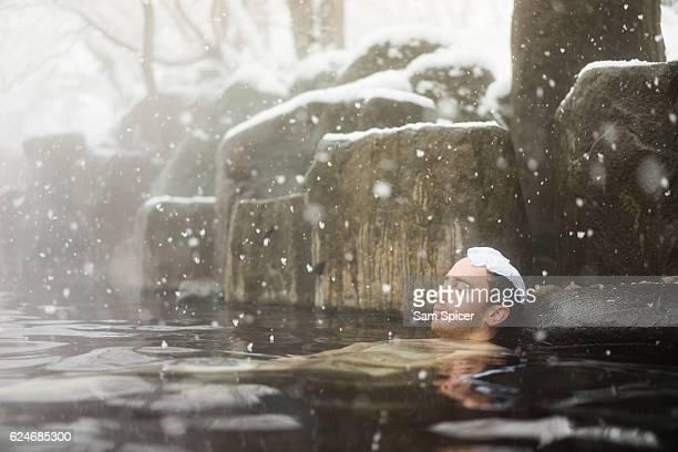 Western tourist enjoying natural hot spring onsen during Winter snow