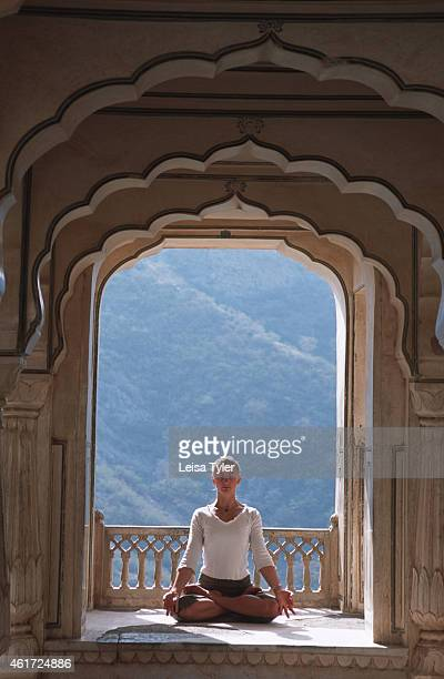 Western tourist practises meditation in a pavillion at Amber Fort a medieval Raput citadel on the outskirts of Jaipur A health regimes originating in...