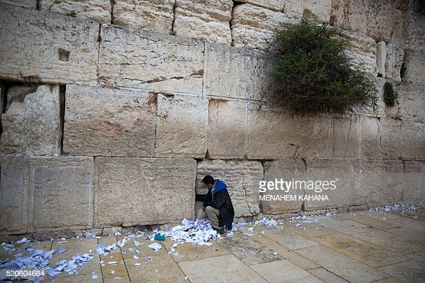 A Western Wall employee removes messages and prayers written on pieces of paper by thousands of people 'addressed to God' from the cracks of the...