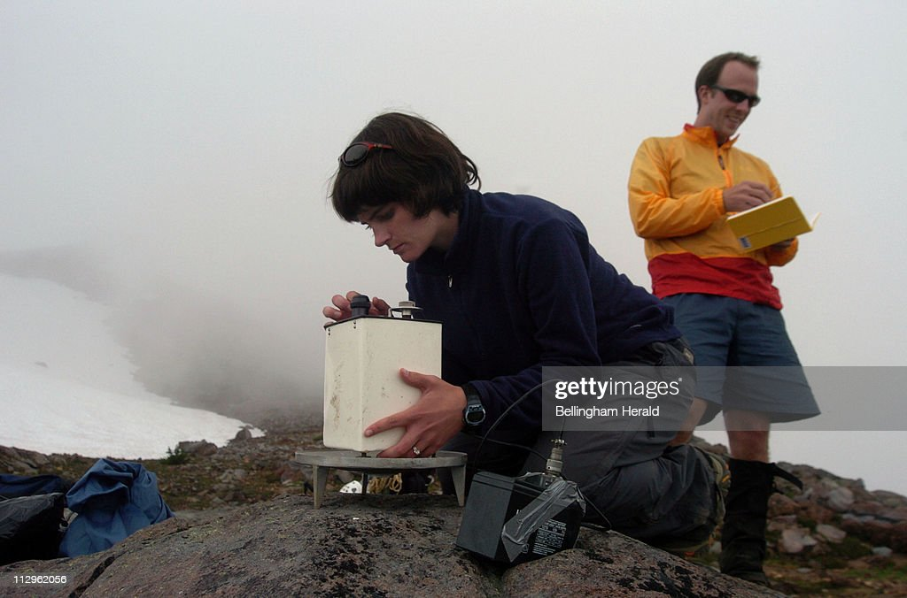 Western Washington University geology graduate student Kristin Hill, foreground, uses a gravimeter to test the gravity on the east side of Mount Baker, July 28, 2006, as fellow geology graduate student Mike Johnsen records the data. The two were part of a group of researchers studying Mount Baker to see how active the volcano remains.