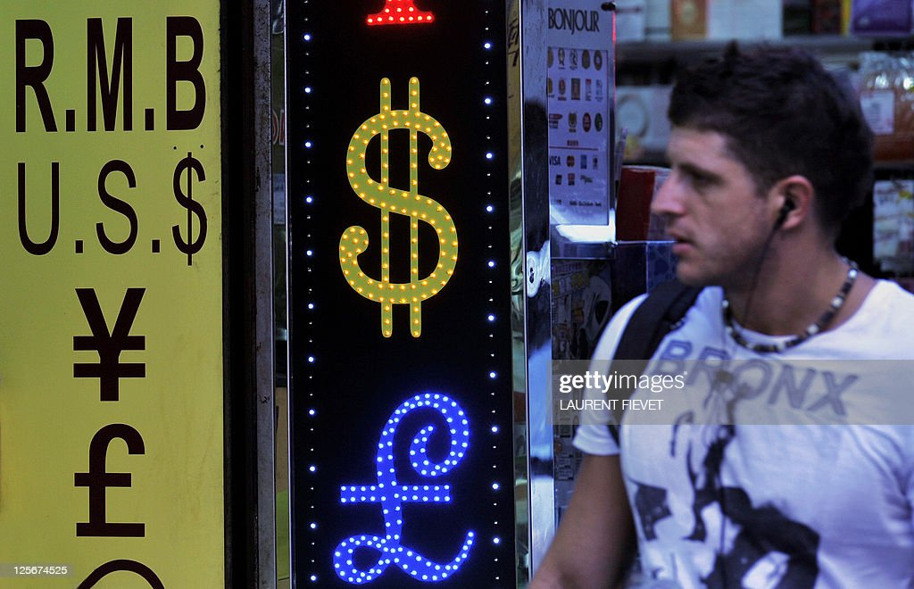 A westerner walks past a currency exchange shop in Hong Kong on September 15 2011 Hong Kong said it has no plans to unpeg its currency from the US...