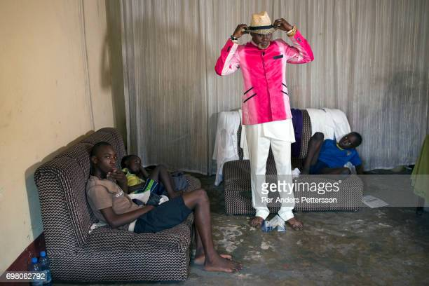 Weston Mwene Kibambe a Sapeur dresses in his favorite suit at home as his sons looks on February 11 2017 in Kinshasa DRC The word Sapeur comes from...