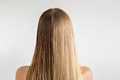 Wet and dry woman's blonde hair before and after using hair dryer on the gray background. Cares about a healthy and clean hair. Beauty salon concept.