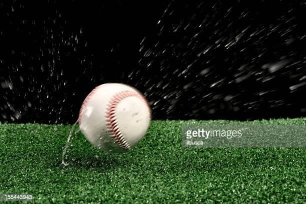 Wet baseball ball bouncing on green artificial grass