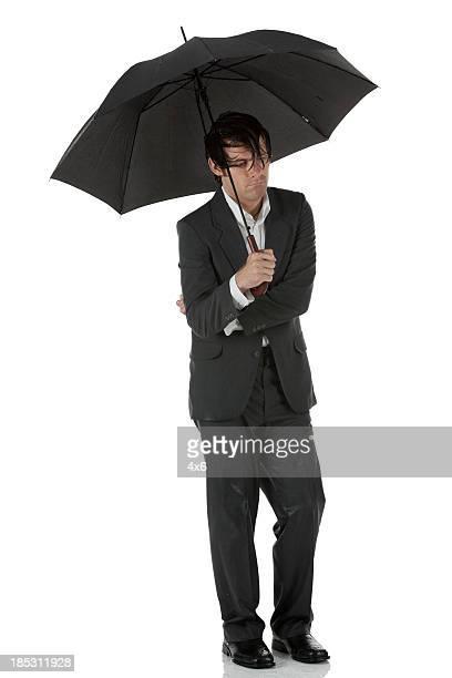 Wet businssman with an umbrella