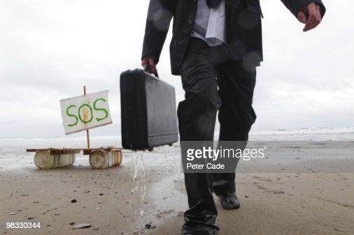 Wet executive walking away from raft, SOS on sail