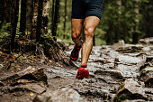 wet feet runner athlete running on trail stones in forest