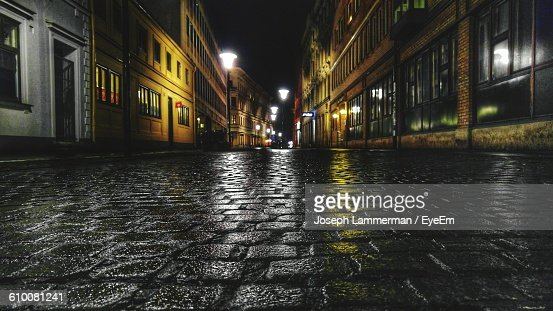 Wet Footpath Amidst Buildings At Night