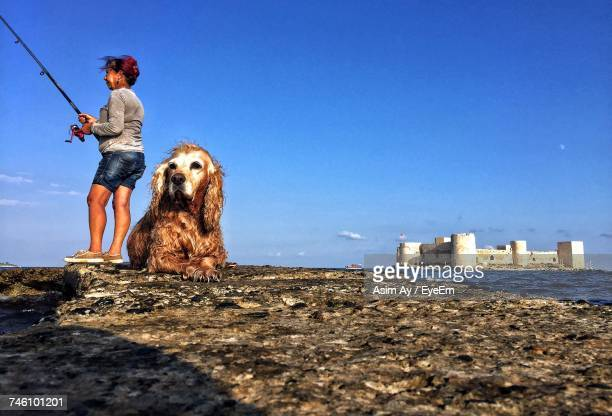 Wet Golden Retriever Lying By Woman Fishing On Pier Against Blue Sky