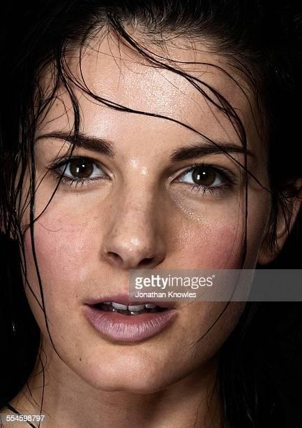 Wet hair falling on female's wet face