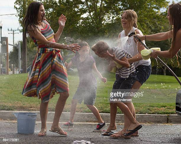 Wet laughing family playing in spraying water hose in park