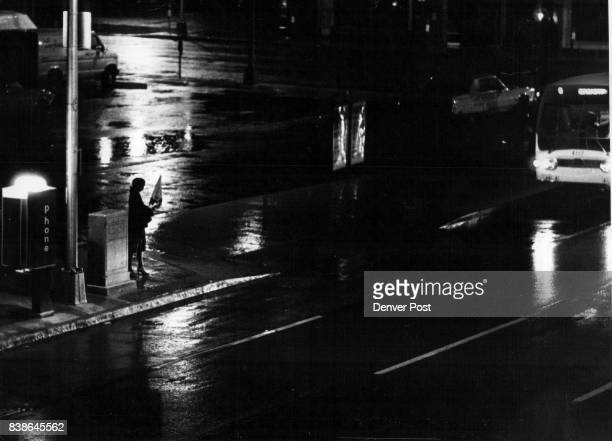 Wet Reflections Rain wet pavement the reflection of headlights in the water a woman with her umbrella at the ready all typified Denver Wednesday...