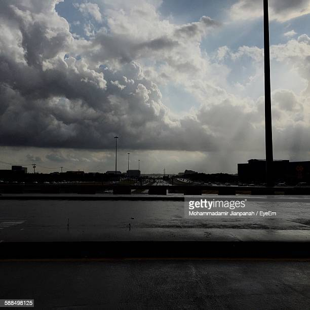 Wet Road Against Cloudy Sky In City During Rainy Season