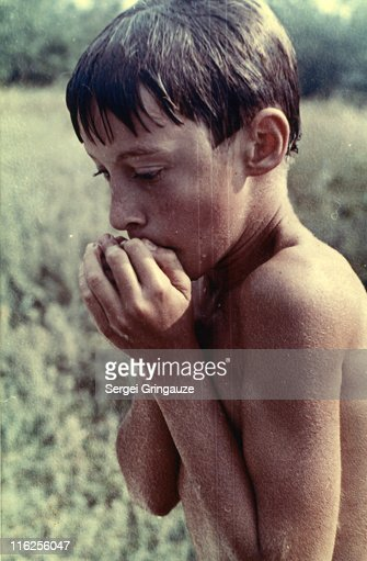 Wet shirtless boy shivering in cold : Stock Photo