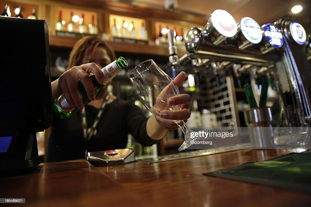 Wetherspoon Plc employee pours Becks lager from a bottle into a glass behind the bar at one of the company's pubs in London, U.K., on Friday, Sept. 13, 2013. JD Wetherspoon, who reported full year sales today, are planning to move into the Irish market next year, Chairman Tim Martin said in a recent interview. Photographer: Matthew Lloyd/Bloomberg via Getty Images